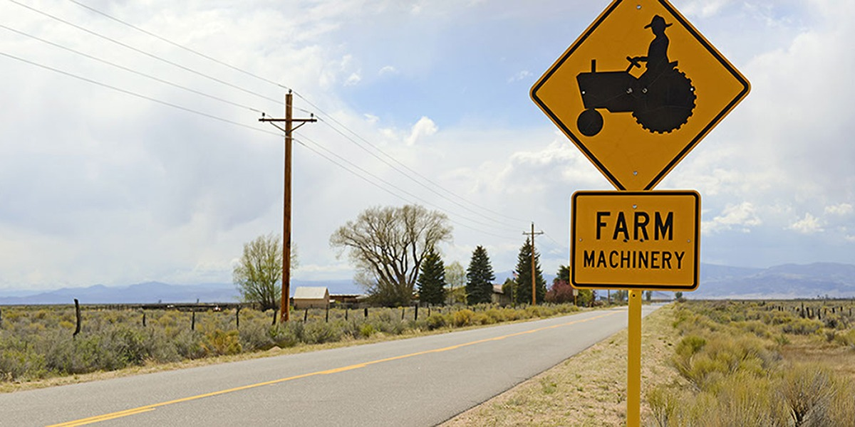 Yellow sign on road saying Farm Machinery